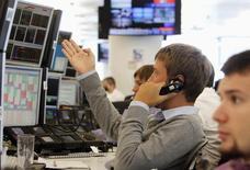 Трейдеры в торговом зале инвестбанка Ренессанс Капитал в Москве 9 августа 2011 года. Российские фондовые индексы слегка отскочили в начале торгов четверга после снижения накануне, несмотря на продолжающееся падение цен на нефть и курса рубля. REUTERS/Denis Sinyakov