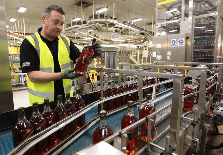 A worker looks at a bottle of Johnnie Walker whisky at the Diageo owned Shieldhall bottling plant in Glasgow, Scotland March 24, 2011. REUTERS/David Moir/Files