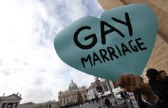 A member of a gay activist group holds a sign in front of St. Peter's square in the Vatican December 16, 2012.   REUTERS/Alessandro Bianchi