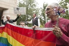 Larry Ferri (R) and Brandi Morris (C) hold large rainbow flag as gay couples marry outside of Mecklenburg County Register of Deeds office in Charlotte, North Carolina, October 13, 2014.    REUTERS/Davis Turner