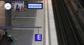 Pasajeros esperan en una plataforma vacía cerca de una pantalla eléctronica que anuncia una huelga de los trabajadores ferroviarios en una estación de Berlín.  Octubre 18, 2014. REUTERS/Fabrizio Bensch