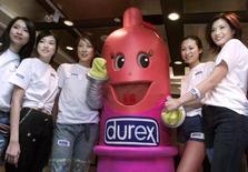 Модели фотографируются с увеличенной копией презерватива Durex на конференции в Гонконге 27 ноября 2001 года. Производитель потребительских товаров Reckitt Benckiser Group увеличил продажи в третьем квартале 2014 года, но они оказались ниже ожиданий из-за слабости европейских рынков и замедления закупок средств от простуды американскими ритейлерами. REUTERS/Kin Cheung