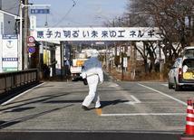 Um agente de descontaminação caminha em frente à entrada da cidade vazia de Futaba, perto da usina nuclear Fukushima Daiichi, atingida por um terremoto seguido de tsunami. 11/03/2014  REUTERS/Toru Hanai