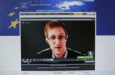 """Accused government whistleblower Edward Snowden is seen on the computer screen of a journalist on the internet site of the Council of Europe, as he speaks via video conference with members of the Committee on legal Affairs and Human Rights of the Parliamentary Assembly of the Council of Europe during an hearing on """"mass surveillance"""" in Strasbourg, April 8, 2014. REUTERS/Vincent Kessler"""