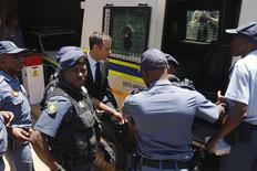 South African Olympic and Paralympic sprinter Oscar Pistorius (C) enters a police van after his sentencing at the North Gauteng High Court in Pretoria October 21, 2014. REUTERS/Siphiwe Sibeko