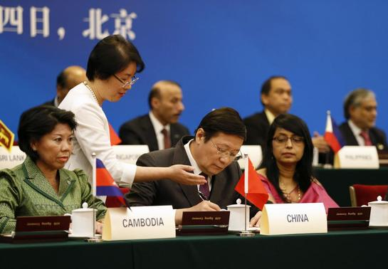 China's Finance Minister Lou Jiwei (C) signs a document, with the guests of the signing ceremony of the Asian Infrastructure Investment Bank at the Great Hall of the People in Beijing October 24, 2014. REUTERS-Takaki Yajima-Pool