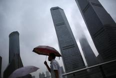 Un hombre camina bajo la lluvia en el distrito financiero de Pudong en el centro de Shanghai. Imagen de archivo, 18 agosto, 2014. La economía de China se expandiría este año a su ritmo más débil en 24 años y se desacelería más en 2015 por una ralentización del sector inmobiliario y un exceso en la capacidad fabril, en momentos en que importantes líderes presionan por reformas estructurales, mostró el viernes un sondeo de Reuters.  REUTERS/Carlos Barria
