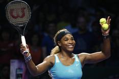 Serena Williams of the U.S. celebrates her win over Eugenie Bouchard of Canada during their WTA Finals singles tennis match at the Singapore Indoor Stadium October 23, 2014. REUTERS/Edgar Su