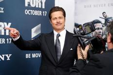 "Cast member Brad Pitt points out former U.S. Secretary of State Colin Powell (not pictured) to photographers as he arrives on the red carpet at the premiere of World War II film ""Fury"" at the Newseum in Washington October 15, 2014.  REUTERS/Jonathan Ernst"