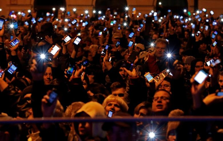 People hold up their mobile phones as they protest against a new tax on Internet data transfers in the centre of Budapest October 26, 2014. REUTERS/Laszlo Balogh