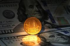 Монета 10 рублей и банкноты 100 долларов США в Санкт-Петербурге 22 октября 2014 года. Рубль торгуется в минусе утром понедельника, но спрос на валюту пока  в основном компенсируется продажей экспортной выручки под крупные налоги. REUTERS/Alexander Demianchuk
