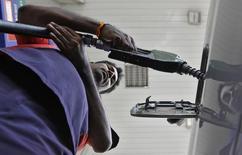 Рабочий заправляет автомобиль на АЗС в Ченнае 18 января 2013 года. Индийская Oil and Natural Gas Corp (ONGC) на фоне падения цен нефти рассчитывает более чем удвоить её добычу за рубежом к 2018 году и рассматривает покупку активов во всех частях земного шара, от бывшего СССР до США. REUTERS/Babu