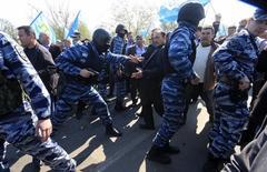 Сотрудники милиции блокируют дорогу крымским татарам, направляющимся на встречу с главой меджлиса Мустафой Джемилевым, у Армянска 3 мая 2014 года. Верховный комиссар Совета Европы по правам человека призвал предпринять срочные меры, обнаружив серьезные нарушения прав человека в Крыму, которые начались с того момента, как в феврале украинский полуостров стал переходить под контроль России. REUTERS/Stringer