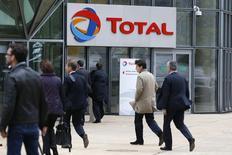 Personas caminan frente la entrada de las oficinas de Total en el distrito financiero de La Défense, cerca de París. Imagen de archivo, 21 octubre, 2014. La petrolera francesa Total anunció el miércoles que continuará controlando los gastos después de que una caída en los precios del petróleo redujera sus ganancias del tercer trimestre. REUTERS/Charles Platiau