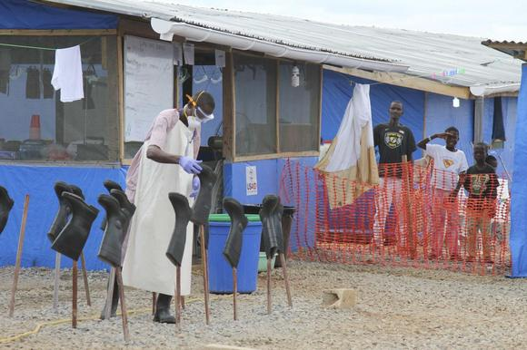 Boys Solomon (C, rear) and Joe (R, rear) stand in the ''red zone'' where they are being treated for Ebola at the Bong County Ebola Treatment Unit about 200 km (120 miles) east of the capital, Monrovia, in this October 28, 2014 file photo. REUTERS/Michelle Nichols/Files