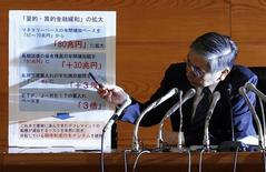 Bank of Japan (BOJ) Governor Haruhiko Kuroda points to a placard showing BOJ policy decisions during a news conference at the BOJ headquarters in Tokyo October 31, 2014. REUTERS/Issei Kato