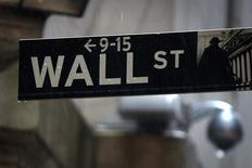 Una señalética de Wall Street es fotografiada bajo la lluvia en las afueras de la bolsa de Nueva York. Imagen de archivo, 09 junio, 2014.  Las acciones bajaban levemente el martes en la apertura de la bolsa de Nueva York, ya que los inversores hacían una pausa tras los continuos avances récord registrados por los principales índices, en una sesión en la que los papeles de energía bajaban por una fuerte caída en los precios del crudo. REUTERS/Carlo Allegri