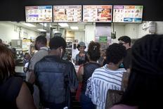 Unas personas en la fila de atención de un restaurante de la cadena Burger King en Nueva York, ago 25 2014. El Instituto de Gerencia y Abastecimiento de Estados Unidos (ISM, por sus siglas en inglés) dijo que la tasa de crecimiento del sector servicios del país se desaceleró más de lo esperado en octubre, anotando la segunda caída mensual consecutiva, al mínimo desde junio.    REUTERS/Carlo Allegri