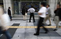 Personas observan una pantalla electrónica que muestra índices económicos en Tokio. Imagen de archivo, 20 octubre, 2014. Las bolsas de Asia caían el jueves luego de que los precios de una serie de materias primas retrocedieron por las preocupaciones sobre la desaceleración del crecimiento mundial, y la bolsa de Tokio cayó después de registrar fuertes ganancias en un repunte inspirado por el estímulo del Banco de Japón. REUTERS/Yuya Shino