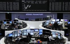 Traders are pictured at their desks in front of the DAX board at the Frankfurt stock exchange November 7, 2014.     REUTERS/Remote/Stringer