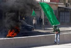 Au point de contrôle de Kalandia, entre Ramallah et Jérusalem. De nouveaux affrontements ont opposé vendredi manifestants palestiniens et forces de sécurité israéliennes à Jérusalem-Est et en Cisjordanie, après deux semaines de tensions autour des lieux saints de l'esplanade des Mosquées. /Photo prise le 7 novembre 2014/REUTERS/Ammar Awad