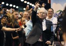 Berkshire Hathaway CEO Warren Buffett points after throwing a newspaper during a competition at a trade show, at the company's annual meeting in Omaha, Nebraska May 3, 2014. Warren Buffett's Berkshire Hathaway Inc on Friday said quarterly profit declined 4 percent, falling short of analyst forecasts, as earnings from insurance underwriting declined and bad weather disrupted shipping at its BNSF Railway unit. REUTERS/Rick Wilking(UNITED STATES - Tags: BUSINESS) - RTR3NN77