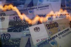 График динамики за год  курса пары рубль/доллар на фоне рублевых купюр в Варшаве 7 ноября 2014 года. Рубль резко дорожает утром понедельника на фоне вербальных интервенций высшего политического и экономического руководства страны в поддержку российской валюты и при низкой ликвидности рынка. REUTERS/Kacper Pempel
