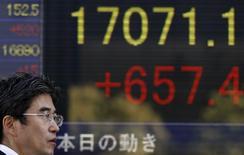 Мужчина у брокерской конторы в Токио 4 ноября 2014 года. Азиатские фондовые рынки, кроме Японии, выросли в понедельник, в основном за счет новостей с саммита АТЭС в Китае. REUTERS/Yuya Shino