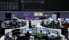 Traders are pictured at their desks in front of the DAX board at the Frankfurt stock exchange November 11, 2014.     REUTERS/Remote/Stringer