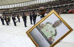 A man holds a framed picture of  South African national soccer team goalkeeper and captain, Senzo Meyiwa during his funeral service in Durban November 1, 2014. REUTERS/Siphiwe Sibeko