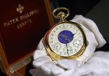 """A staff member holds """"The Henry Graves Supercomplication"""" handmade watch by Patek Philippe at Sotheby's auction house in Geneva in this November 5, 2014 file photo. REUTERS/Denis Balibouse/Files"""