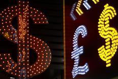 Символы доллара США и других валют у обменного пункта в Гонконге 1 ноября 2014 года.  Мировые регуляторы назначили штрафы на общую сумму $3,4 миллиарда пяти крупным банкам: UBS, HSBC, Citigroup, Royal Bank of Scotland и JP Morgan, наказав их за манипуляции на валютном рынке. REUTERS/Damir Sagolj