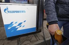 Водитель заправляет автомобиль на АЗС Газпромнефти в Москве 12 ноября 2013 года. Газпромнефть, нефтяное крыло Газпрома, нарастила чистую прибыль по МСФО за девять месяцев текущего года на 3 процента в годовом выражении до 139,5 миллиарда рублей. REUTERS/Maxim Shemetov