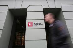 Мужчина проходит мимо здания Московской биржи 7 ноября 2014 года. Российские фондовые индексы начали торги четверга с разнонаправленных движений на фоне скромных колебаний рубля. REUTERS/Maxim Shemetov