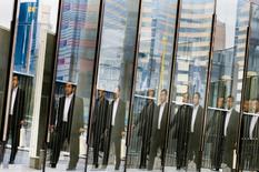 Men are reflected in a glass railing as they walk at the Shiodome business district in Tokyo November 12, 2014. REUTERS/Thomas Peter
