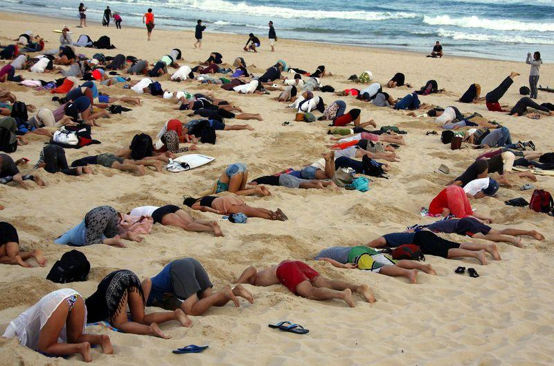 australians bury heads in sand to mock government climate stance