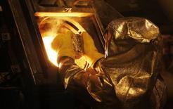 """Un técnico coloca un """"botón"""" de oro en un horno refinador en la mina Carlin en Elko, EEUU, mayo 21 2014. La demanda global de oro bajó a su nivel más bajo en casi cinco años durante el tercer trimestre, ya que las compras desde China disminuyeron en un tercio, informó el jueves el Consejo Mundial del Oro (WGC). REUTERS/Rick Wilking"""