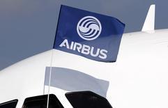 Инженер по летным испытаниям держит флаг Airbus Group после первого полета Airbus A320neo  (New Engine Option) в городе Коломье под Тулузой 25 сентября 2014 года. Крупнейшая в Европе аэрокосмическая группа - Airbus Group сообщила в пятницу о росте прибыли за 9 месяцев на 12 процентов за счет хороших показателей дивизионов по производству самолетов и вертолетов и подтвердила прогноз прибыли на год. REUTERS/Regis Duvignau