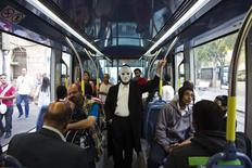 Passengers, one wearing a mask, ride a light rail tram in Jerusalem November 11, 2014. REUTERS/Ronen Zvulun