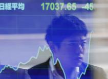 Un transeúnte  reflejado en una pantalla electrónica que muestra el índice Nikkei en Tokio, 17 noviembre, 2014. Las acciones japonesas anotaron el lunes su mayor declive diario desde agosto, y el yen rebotaba desde el mínimo en siete años contra el dólar que tocó después de que datos reportados en la sesión revelaron que Japón cayó en una recesión en el tercer trimestre. REUTERS/Issei Kato