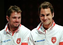 Switzerland's Davis Cup team player Roger Federer (R) smiles next to Stanislas Wawrinka during the draw ceremony at the Victoria Hall in Geneva September 11, 2014. REUTERS/Denis Balibouse