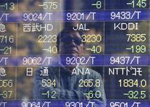 Un hombre se ve reflejado en una pantalla electrónica que muestra índices económicos en Tokio, 17 noviembre, 2014.  Las bolsas de Asia retrocedían el martes en medio de una toma de ganancias en Hong Kong y China continental, y las acciones de Tokio repuntaron por las expectativas de que Japón optará por unas elecciones anticipadas que podrían dar lugar a nuevas medidas de estímulo. REUTERS/Issei Kato