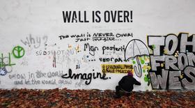 A man sprays graffiti on the legendary John Lennon Wall in the historical centre of Prague November 18, 2014. REUTERS/David W Cerny