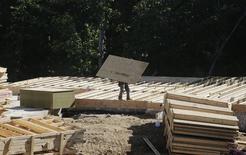 Un carpintero transporta una pieza de piso para la construcción de una vivienda en Brandywine, EEUU, mayo 31 2013. Los inicios de construcciones de casas de Estados Unidos bajaron imprevistamente en octubre, pero un salto en los permisos a un máximo en casi seis años y medio sugirió que el mercado de la vivienda continuaba recuperándose.      REUTERS/Gary Cameron