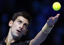 Novak Djokovic of Serbia serves during an exhibition match against Andy Murray of Britain at the ATP World Tour Finals at the O2 in London, November 16, 2014. REUTERS/Suzanne Plunkett