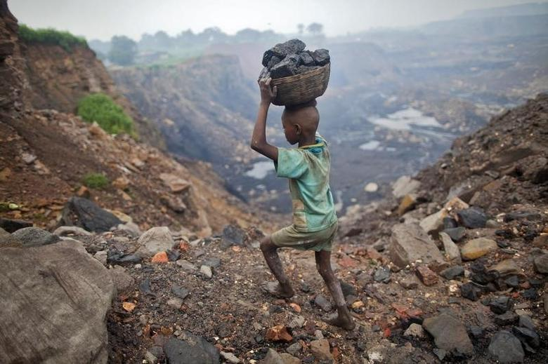 A boy carries coal at an open cast coal field at Dhanbad district in Jharkhand September 20, 2012.REUTERS/Ahmad Masood/Files