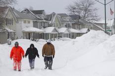 Pedestrians walks a snow-covered street following an autumn snow storm in Lackawanna, near Buffalo, New York November 20, 2014.   REUTERS/Aaron Lynett