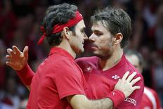 Switzerland's Roger Federer (L) celebrates with his team mate Stanislas Wawrinka after they defeated France's Julien Benneteau and Richard Gasquet during their Davis Cup final doubles tennis match at the Pierre-Mauroy stadium in Villeneuve d'Ascq, near Lille, November 22, 2014. REUTERS/Pascal Rossignol