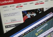 The Ladbrokes (top) and PaddyPower Sport betting websites are seen on electronic devices in this file picture illustration taken in Paris May 22, 2014.  REUTERS/Christian Hartmann/Files