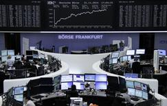 Traders are pictured at their desks in front of the German share price index DAX board at the Frankfurt stock exchange November 21, 2014.     REUTERS/Remote/Stringer
